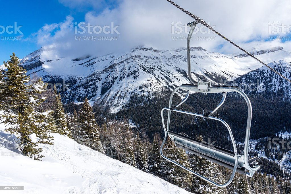 Ski Lift Chair With View of Snowy Mountains stock photo