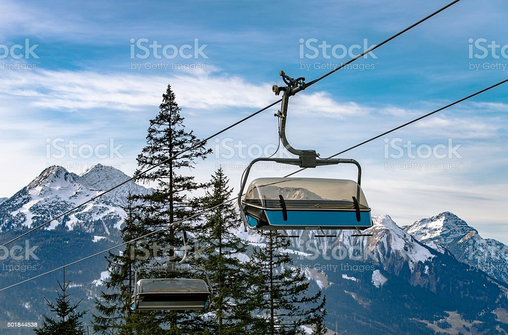 Ski lift chairs on snowy Alps background stock photo