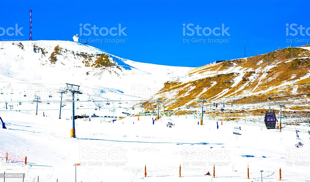 Ski lift with seats going over the mountain and ski tracks stock photo