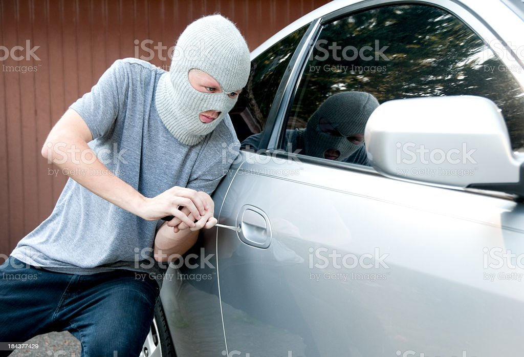 Ski masked teenager breaking into a car royalty-free stock photo