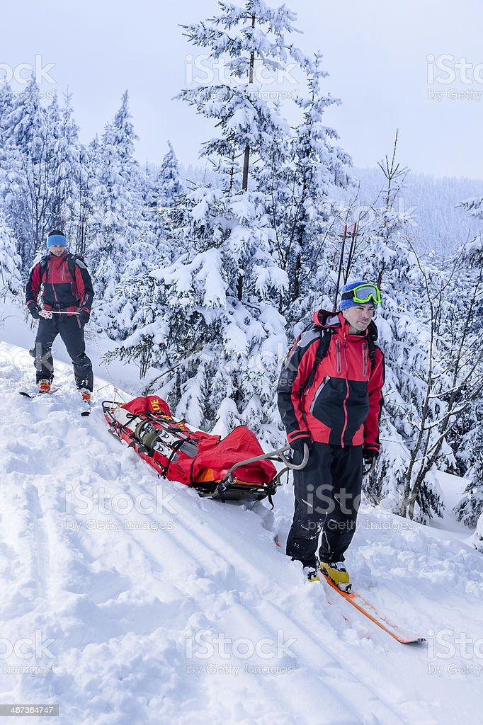 Ski patrol transporting injured skier snow forest stock photo