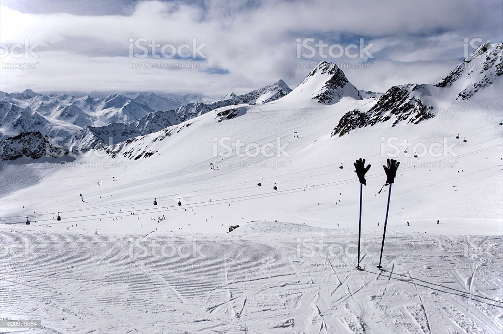 Ski poles, gloves and slopes on Tiefenbach glacier in Solden stock photo