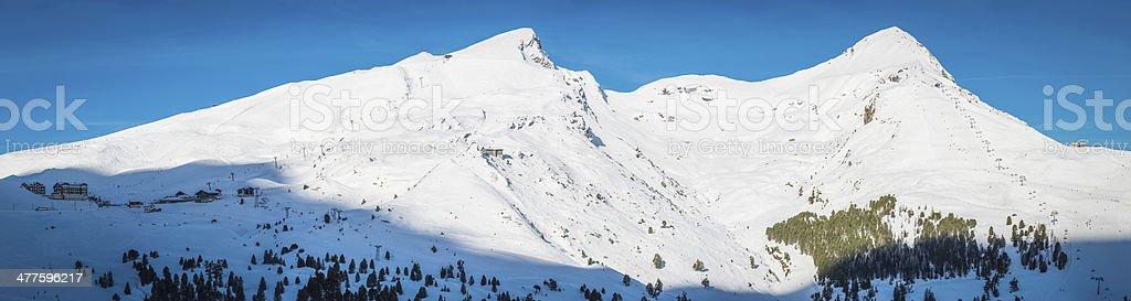 Ski resort Alpine chalets white snowy mountains panorama Alps Switzerland royalty-free stock photo