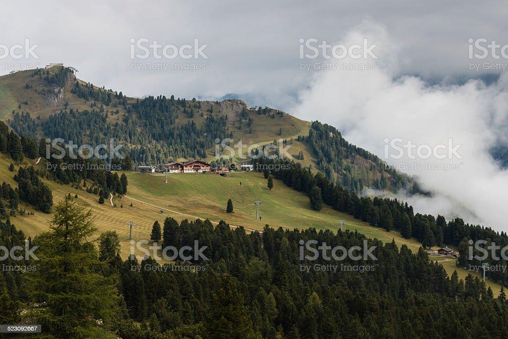 ski resort on forested slope in Dolomites stock photo