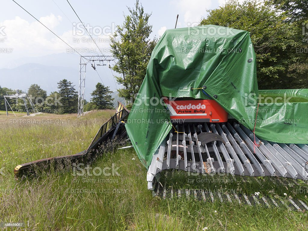Ski resort snowcat parked on green grassy meadow during summer royalty-free stock photo