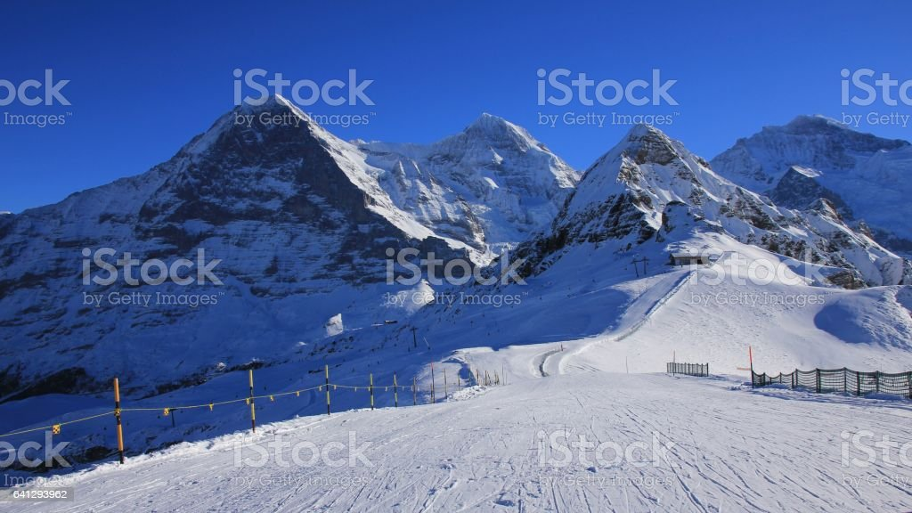 Ski slope and snow covered mountaind Eiger, Monch, Lauberhorn and Jungfrau. stock photo