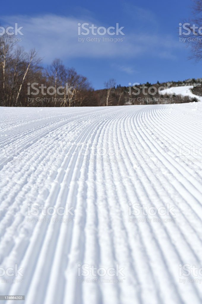 Ski slope groomed to corduroy snow with blue sky royalty-free stock photo