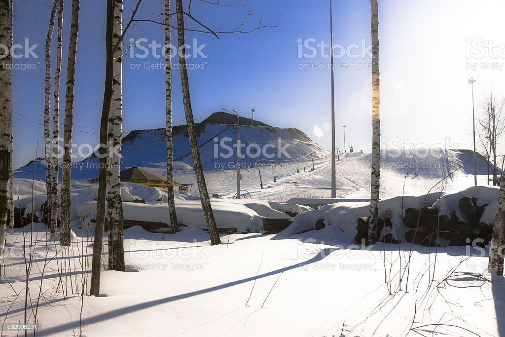 Ski slope on sunset. Descent from snow-covered slope. stock photo