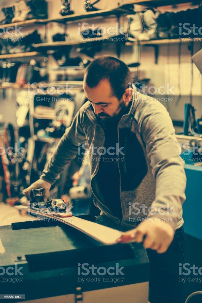Ski tuning and repairs. Winter shop worker doing base repair stock photo