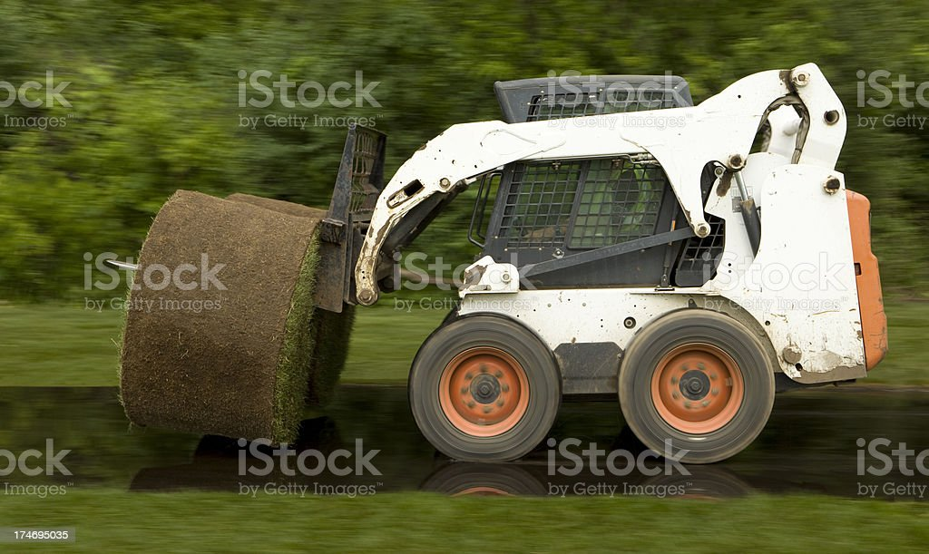 Skid Loader Forklift Transporting Sod on Wet Pavement stock photo