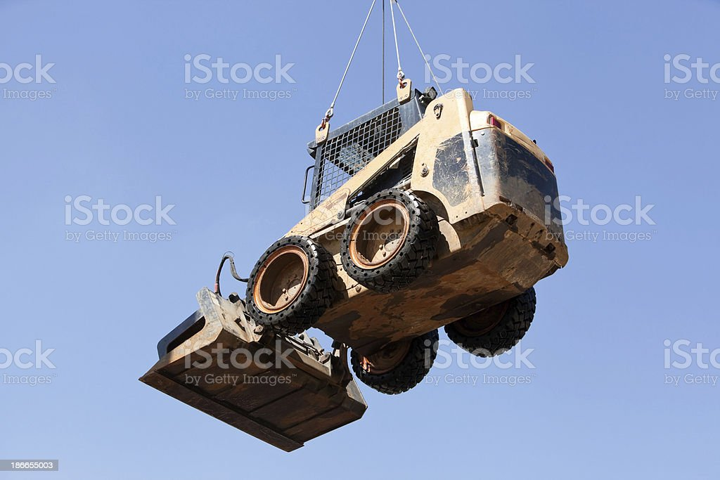 Skid Loader Hanging from Crane Cables against Blue Sky stock photo