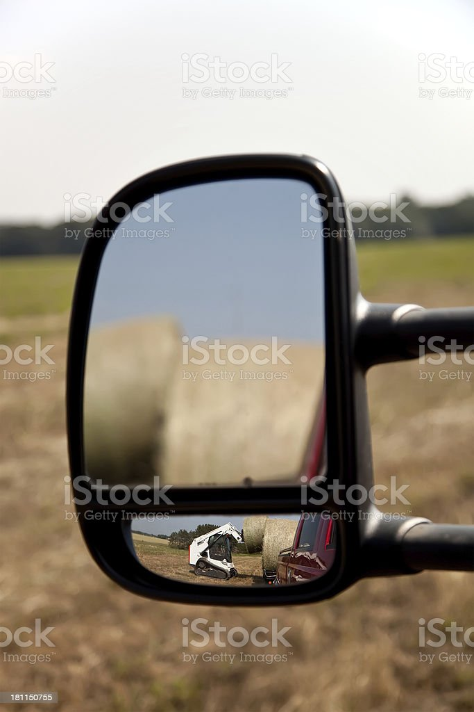 Skid Loader Loading Hay Bales in Mirror stock photo