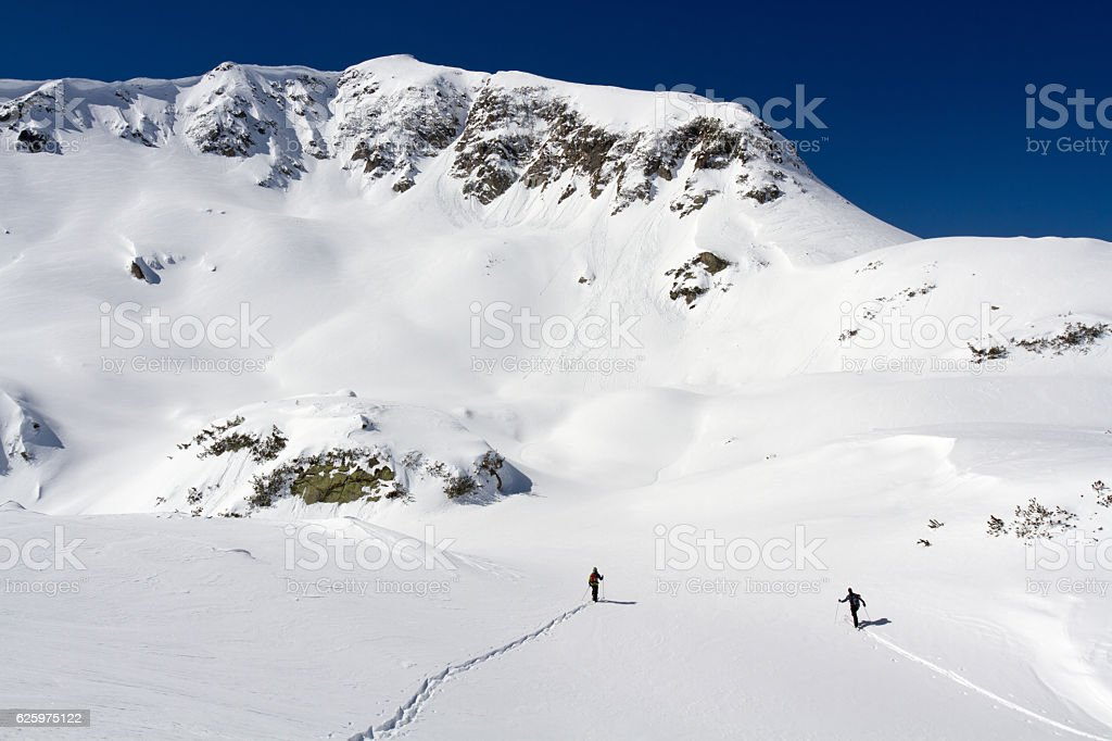 Skier and snowboarder heading up into winter mountain stock photo
