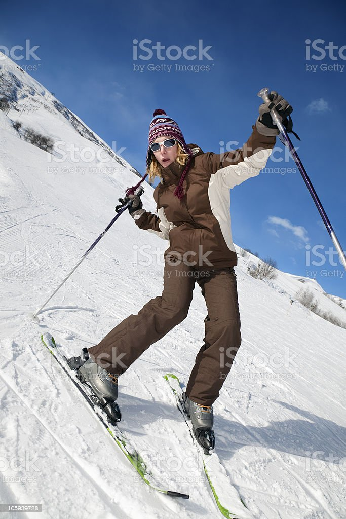 A skier doing a crazy pose as they ski down a snowy mountain stock photo