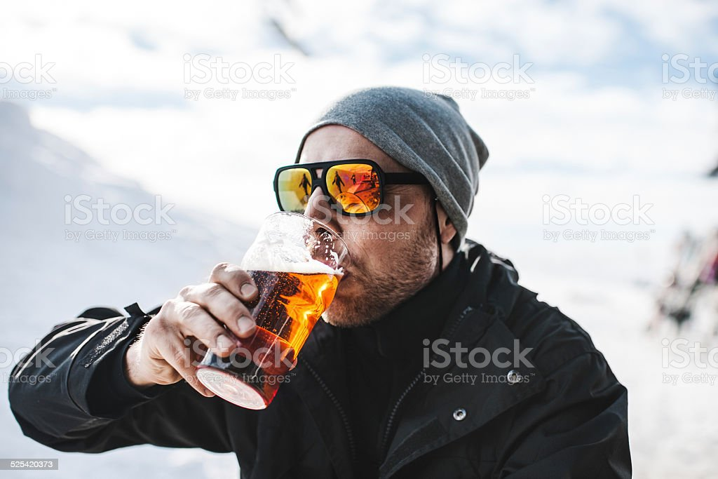 Skier drinking a beer at after ski stock photo