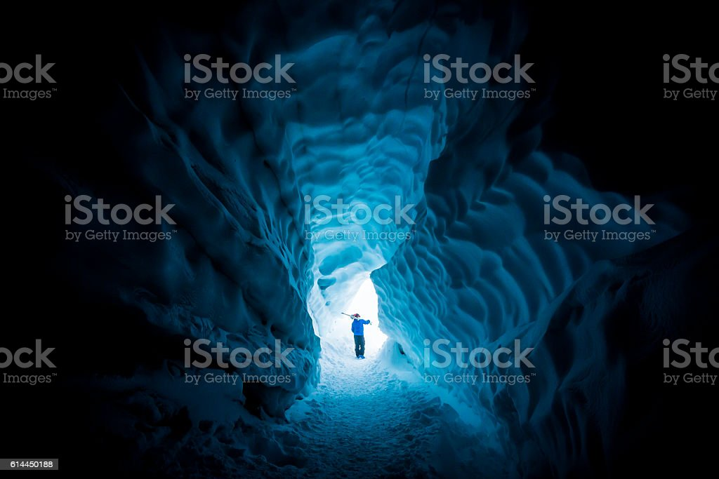 Skier exploring ice cave. stock photo