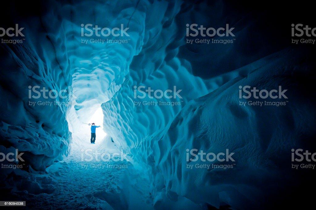 Skier exploring ice cave. stock photo