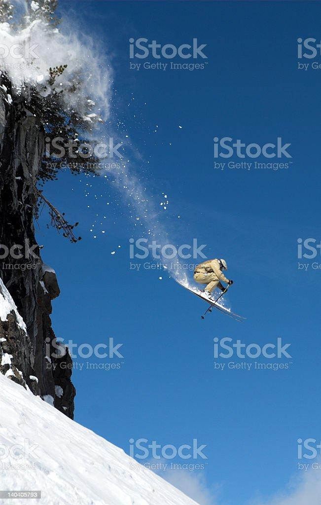 Skier flying off mountain onto slopes royalty-free stock photo