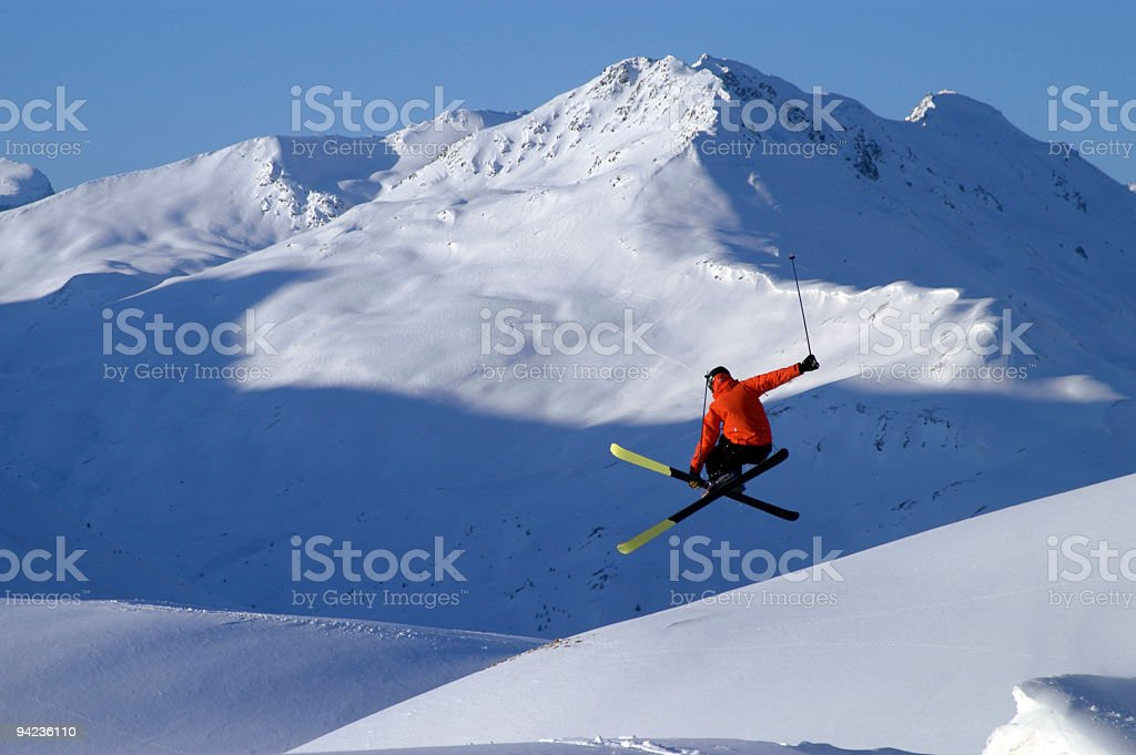 A skier in a red jacket performing a jump royalty-free stock photo