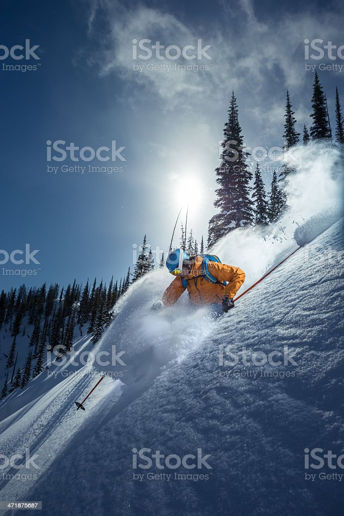 Skier in deep powder snow and trees in the background stock photo