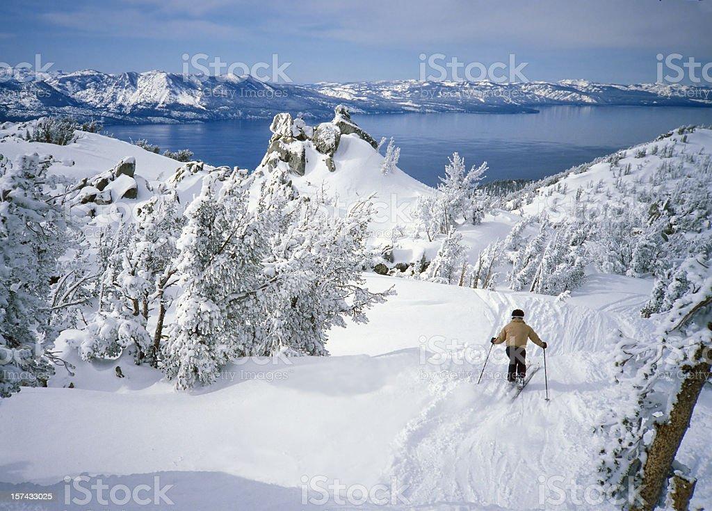 Skier in Fresh Snow Above Alpine Lake Tahoe stock photo