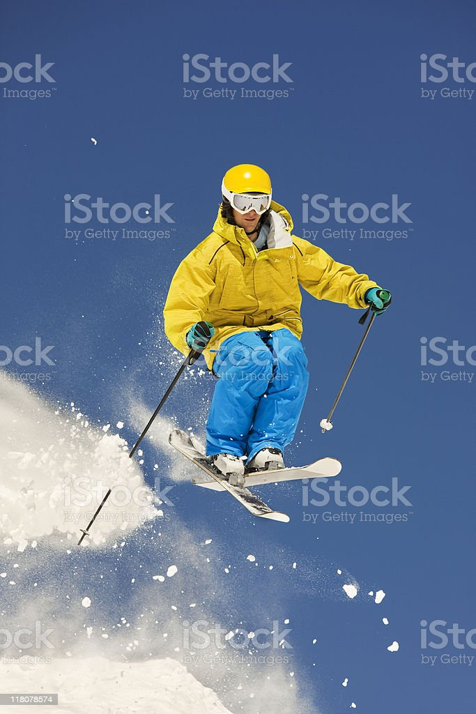 Skier In Mid-Air Making Jump Against Blue Sky royalty-free stock photo