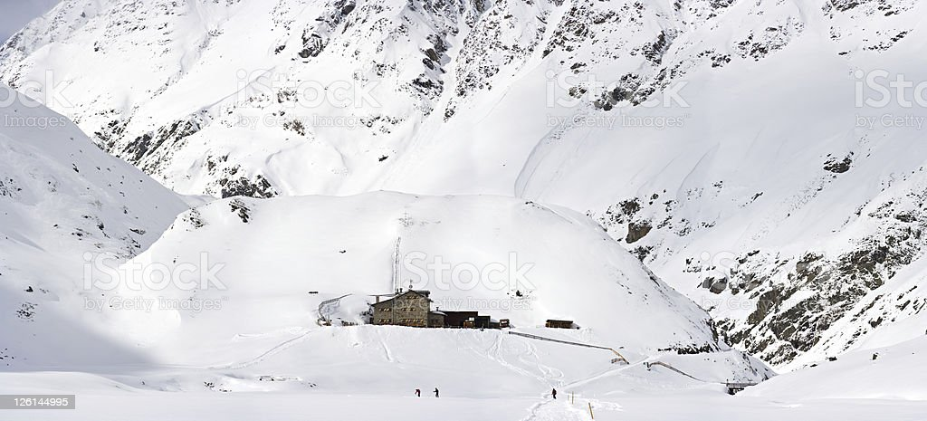 Skier In Winter Valley With Mountain Hut stock photo