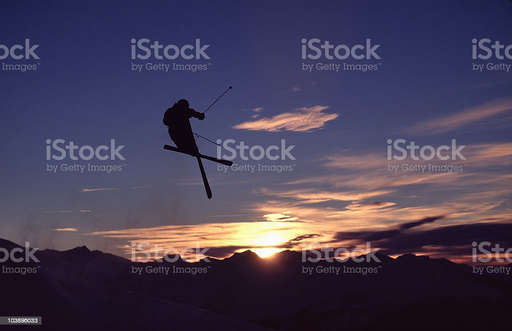 Skier jumping into a mountain sunset. royalty-free stock photo