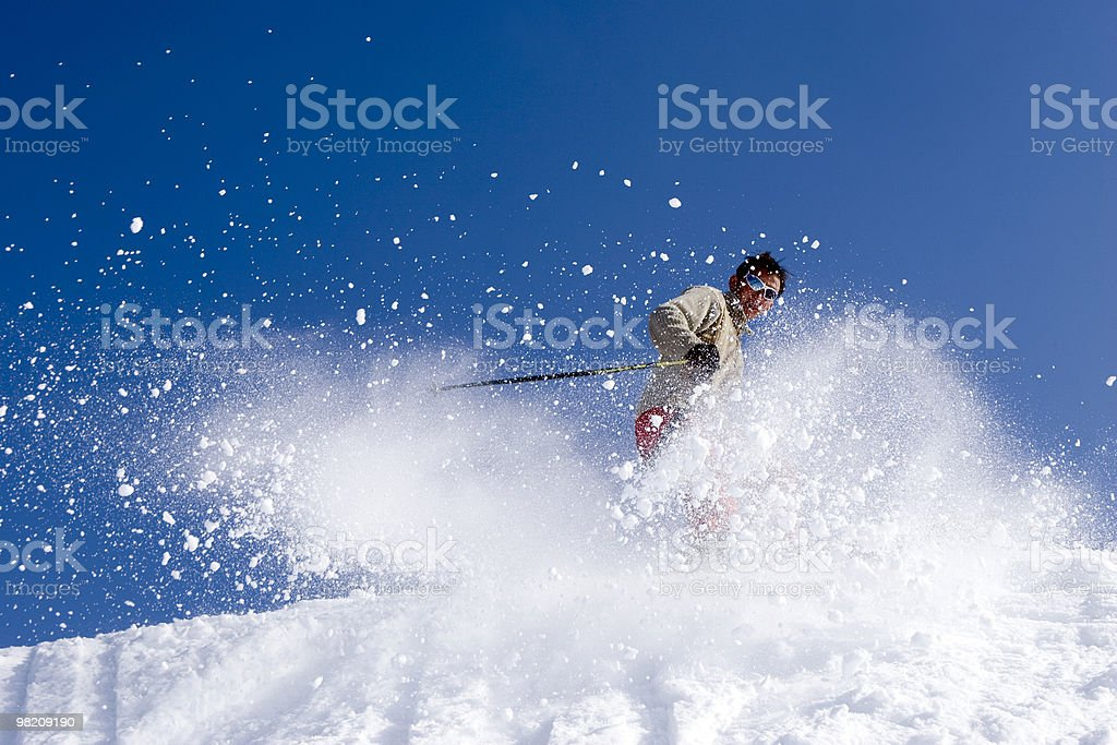 Skier jumping into snow with blue sky royalty-free stock photo