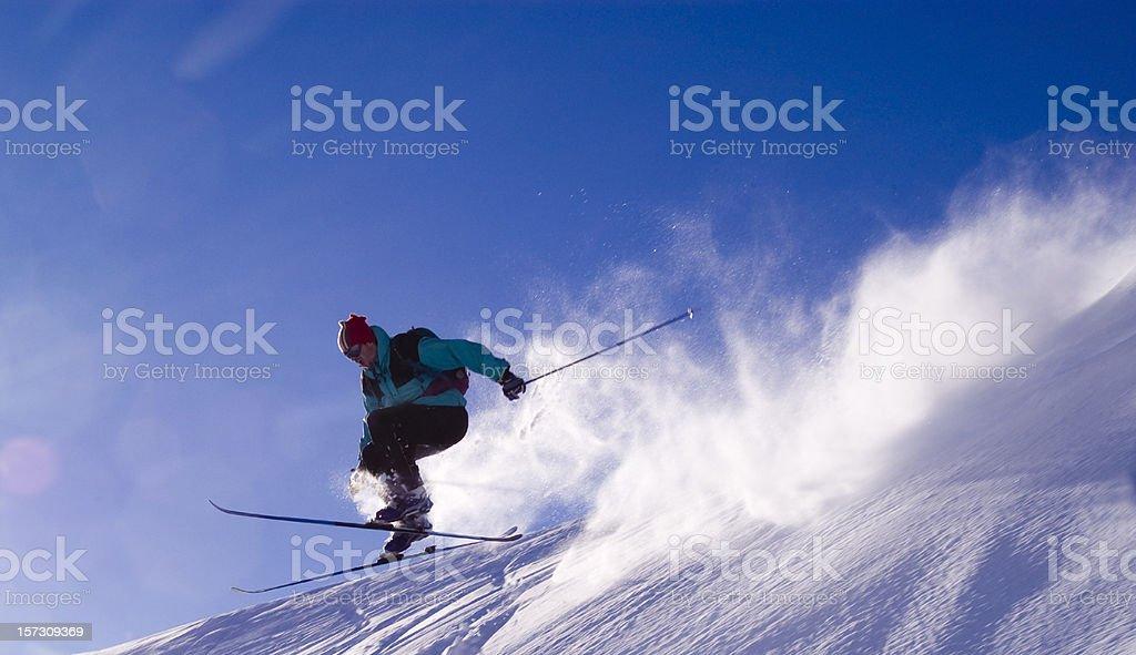 Skier jumping off mountain peak catching big air stock photo