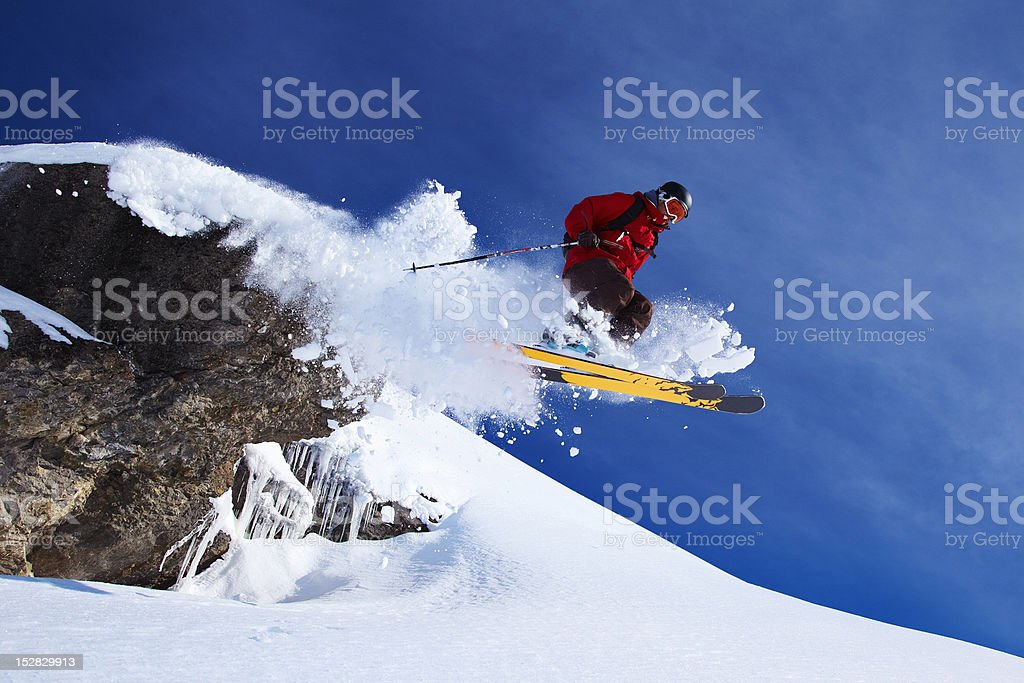 Skier jumping on snowy slope stock photo
