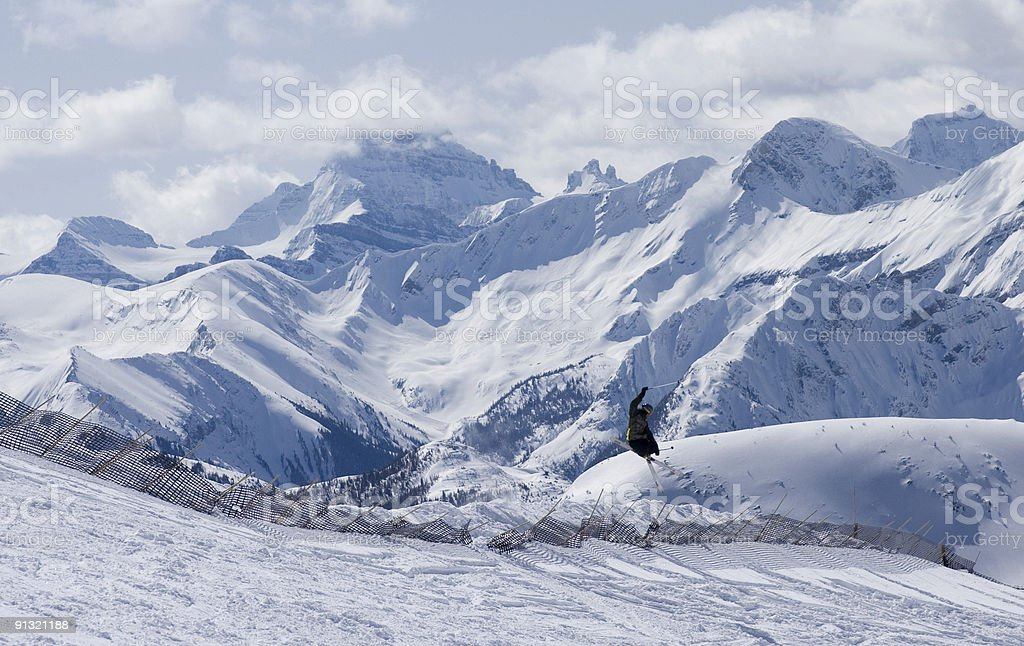 Skier jumping over snow fence stock photo