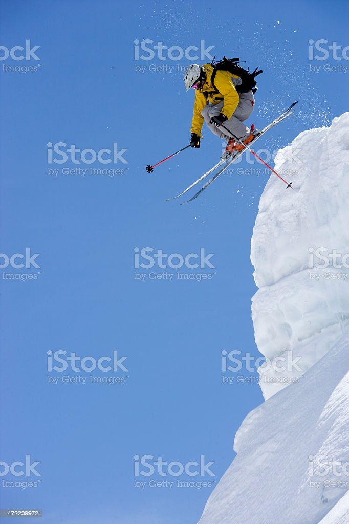 Skier jumps from the edge of snow ridge on glacier. stock photo