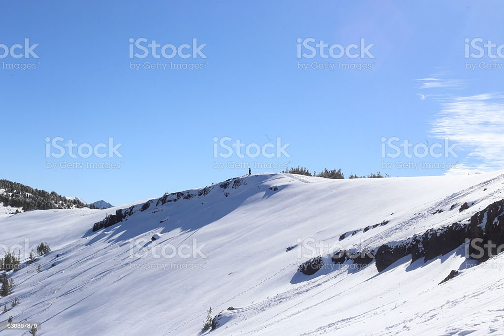 Skier Looking Over Cliffs stock photo