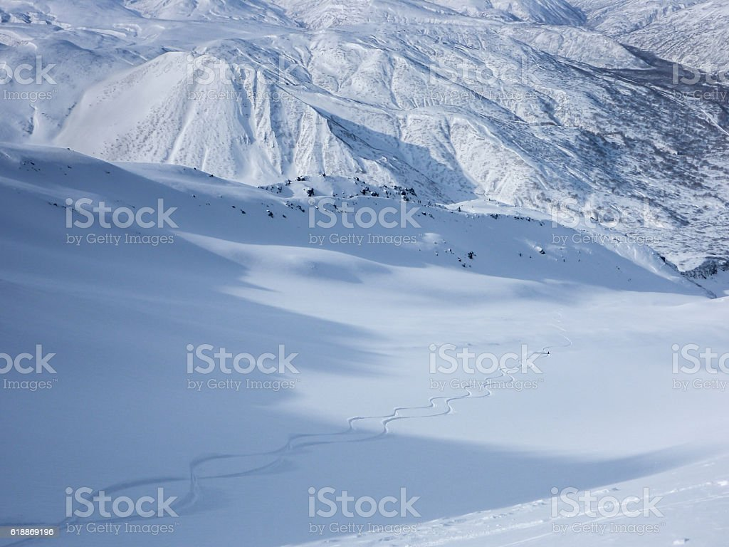 Skier making fresh tracks in untouched snow down a valley stock photo