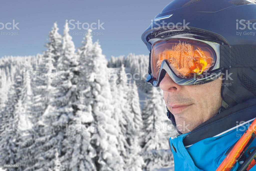 Skier man in the blue skiing jacket, helmet and glasses stock photo