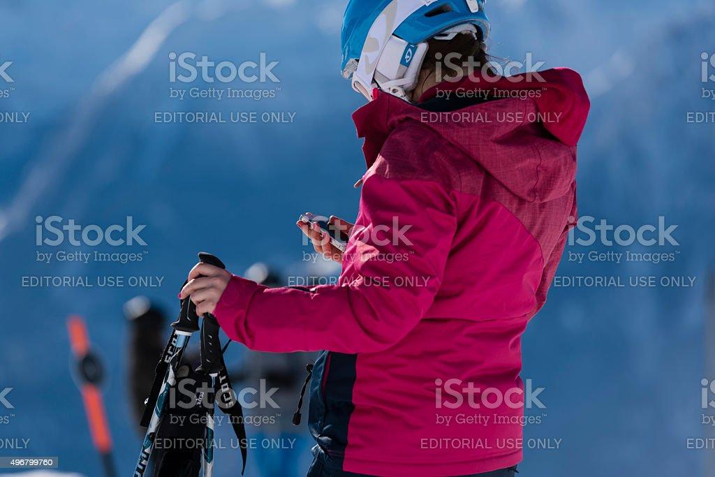 Skier outside in nature on ski piste using mobile phone stock photo