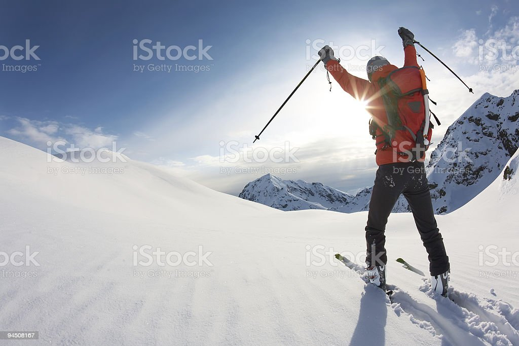 Skier reaches his arms up over a snowy mountain landscape stock photo