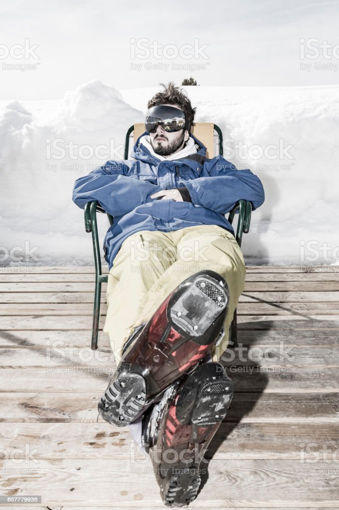 Skier resting on chair stock photo
