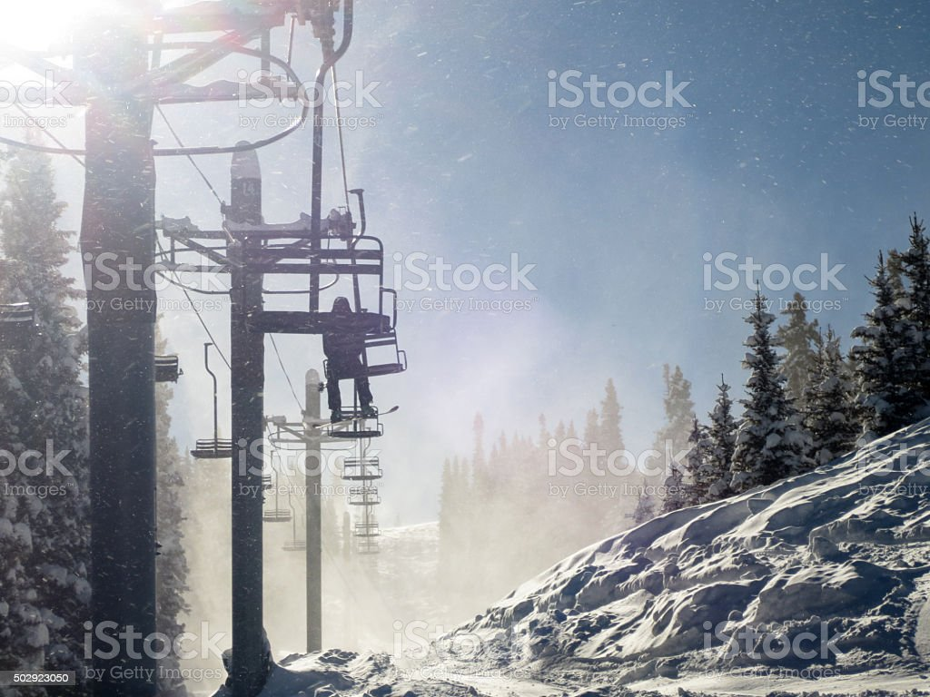 Skier silhouette on chair lift in blowing snow stock photo