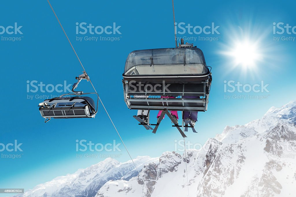Skier sitting at ski lift stock photo