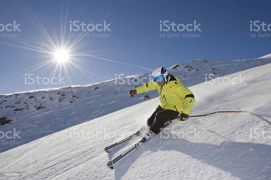 Skier skiing down a mountain in front of the sun stock photo