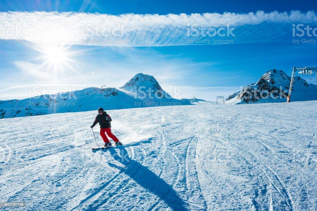 Skier skiing down the slope of ski resort stock photo