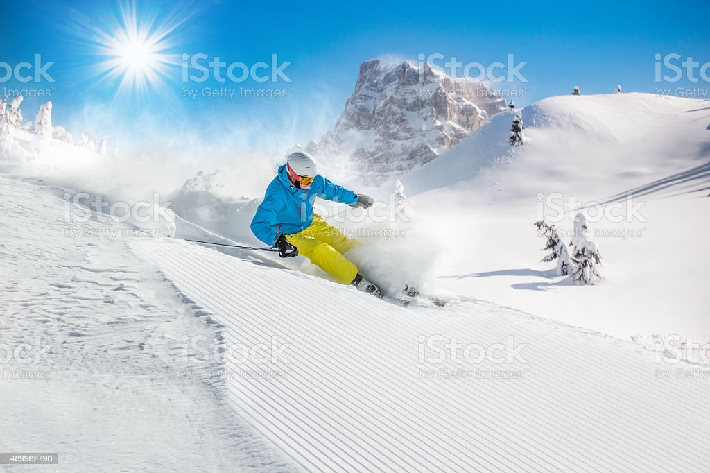 Skier skiing downhill in high mountains stock photo