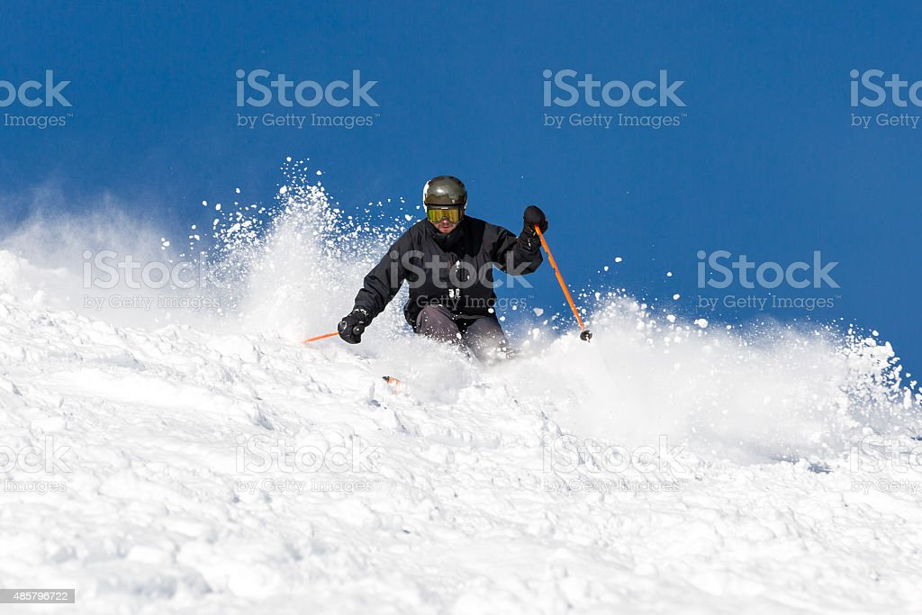 Skier skiing off piste in powder snow stock photo
