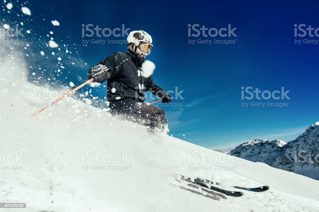 Male skier skiing in fresh snow on ski slope on a sunny winter day at...