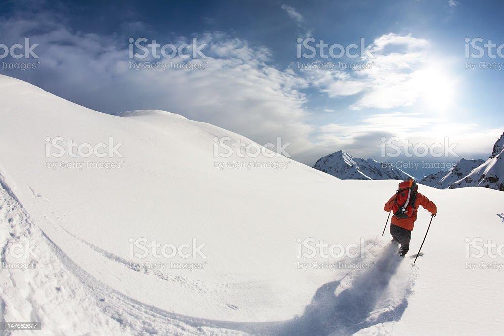 Skier skiing through pristine white snow royalty-free stock photo