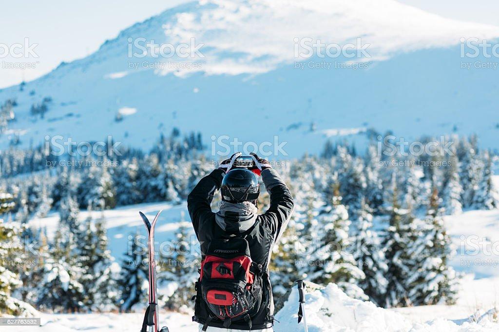 Skier taking photo of the snowy mountain stock photo