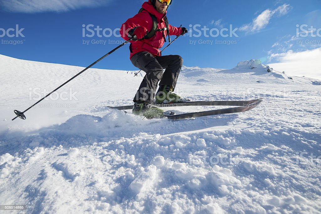 Skier turning on a blue sky day stock photo