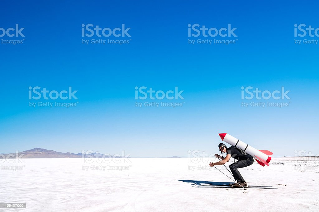 Skier with a rocket on his back on the desert. stock photo